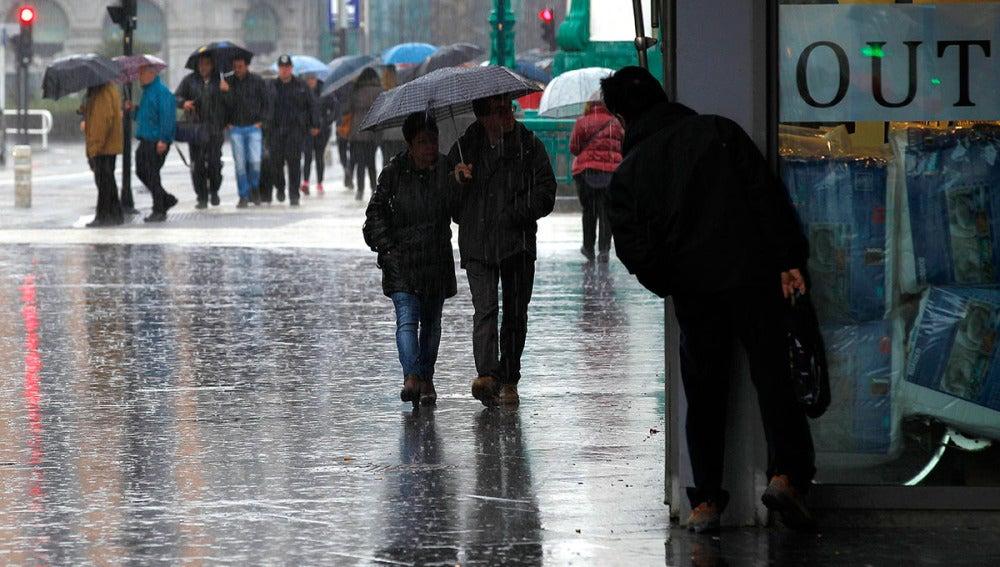 Dos personas pasean bajo la lluvia en San Sebastián
