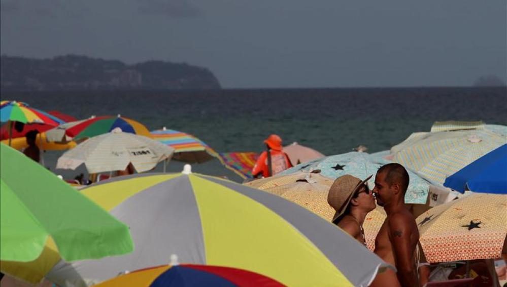 Dos bañistas entre sombrillas en una playa.