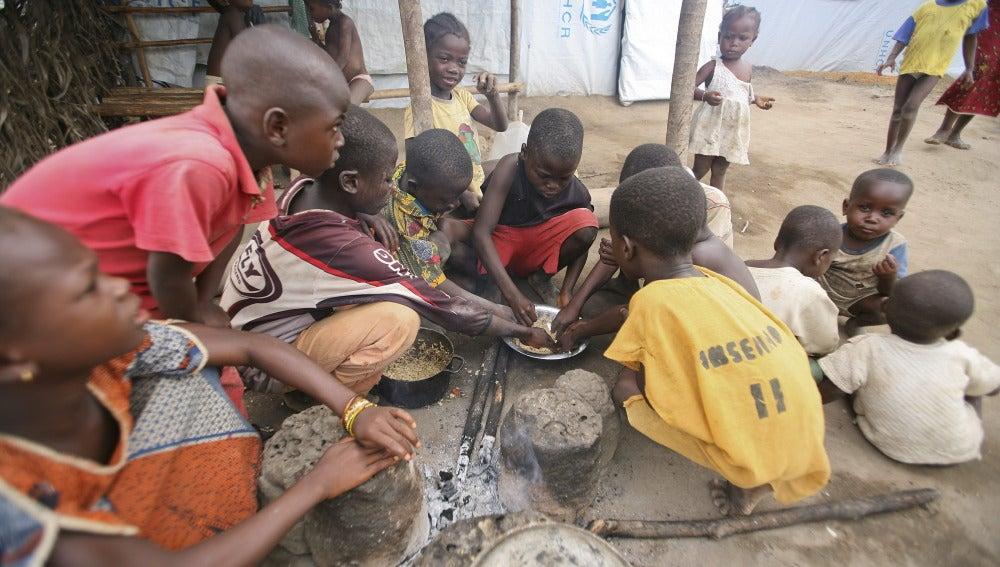 Niños marfileños comen en el campamento de refugiados de Bahn