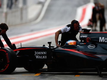 Los mecánicos del McLaren empujan el monoplaza de Alonso dentro del box