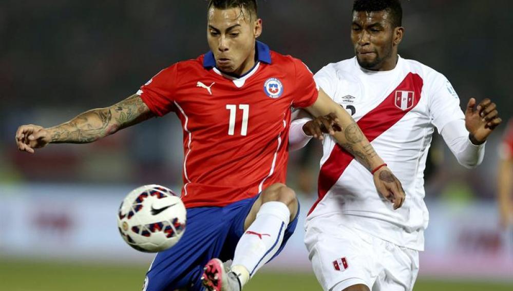 El delantero chileno Eduardo Vargas ante el centrocampista peruano Carlos Antonio Ascues.