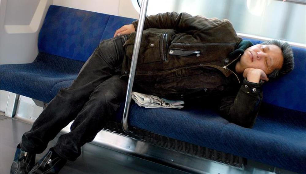 Una mujer echándose la siesta en el metro,