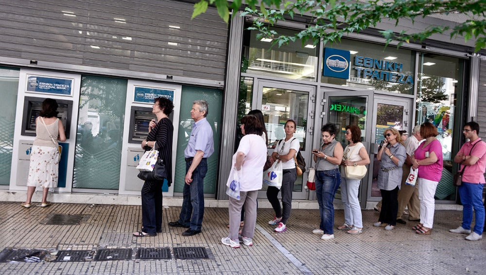 Ciudadanos griegos tratan de sacar dinero en un cajero de Atenas