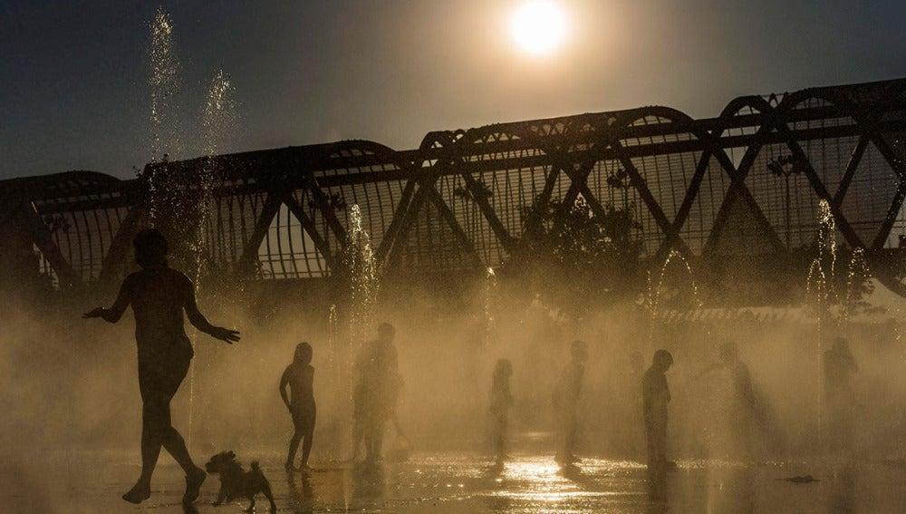 Varias personas se refrescan en las fuentes de Madrid Río