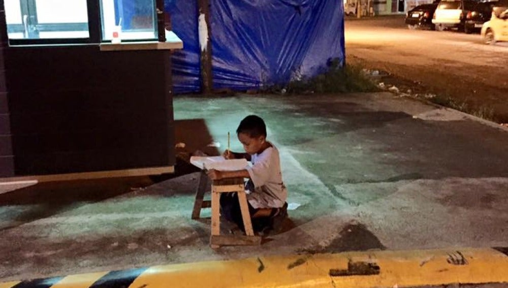 Niño estudiando a la luz de un McDonald's