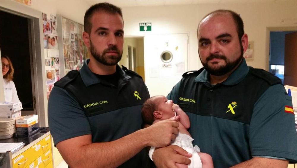 Los dos guardias civiles con la bebé encontrada en un contenedor en Madrid