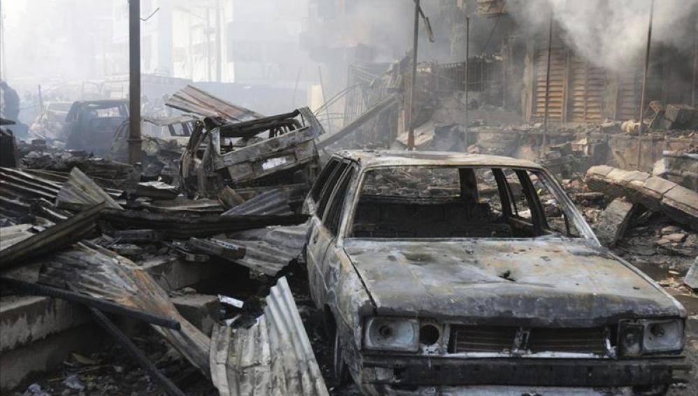 Escombros y coches calcinados por una explosión.