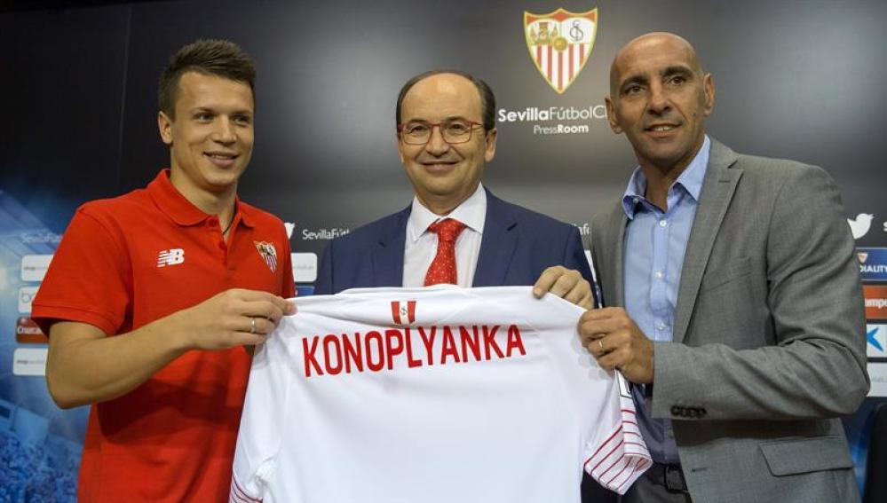 Monchi ayuda a sostener la camiseta de Konoplyanka, un nuevo refuerzo del Sevilla