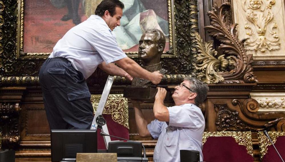 Dos operarios municipales retiran ayer el busto del Rey Juan Carlos I