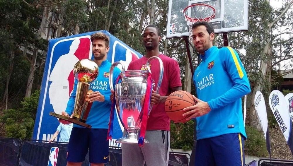 Piqué, Harrison Barnes y Busquets posan con el trofeo de la NBA y de la Champions
