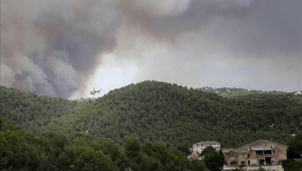 Un helicóptero trabaja cerca de varias viviendas para combatir el incendio