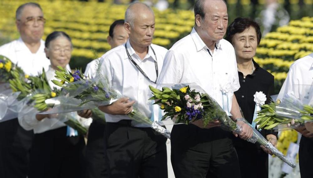 Familiares de las víctimas de la bomba atómica realizan una ofrenda floral