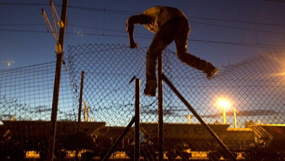 Inmigrante saltando una verja del Eurotunnel