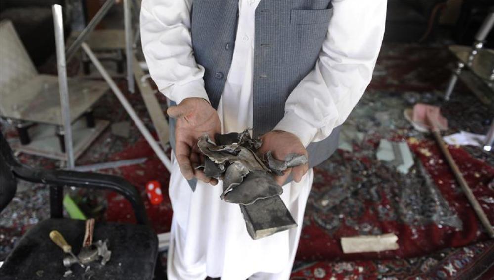 Un hombre muestra restos de objetos que han quedado tras la explosión
