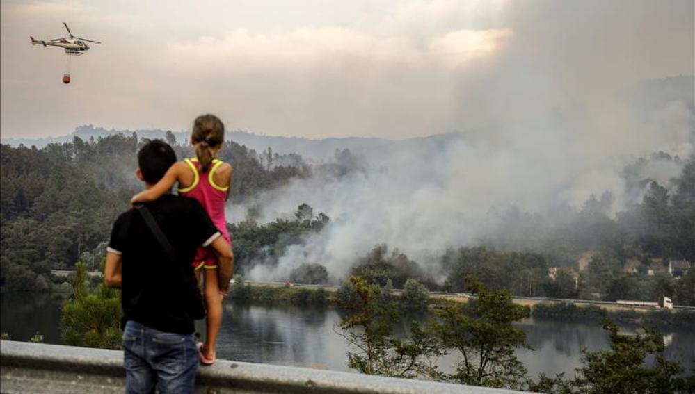 Un helicoptero realiza trabajos de extinción sobre las llamas del incendio declarado el domingo, en el termino municipal orensano de Pereiro de Aguiar.
