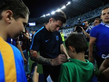 Messi firmando una camiseta