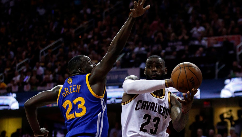 Lebron James penetra a canasta ante la defensa de Draymond Green