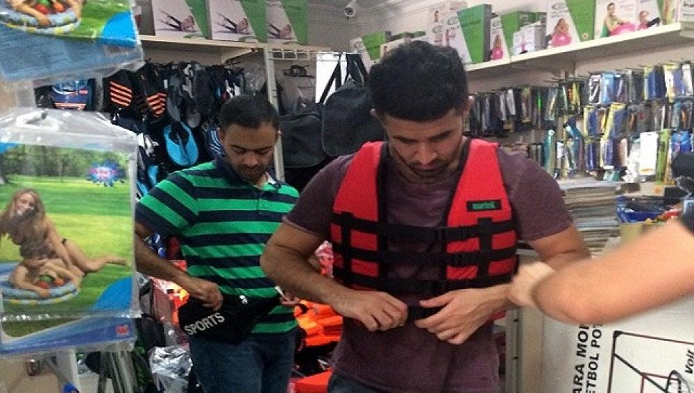 Refugiado comprando un chaleco salvavidas