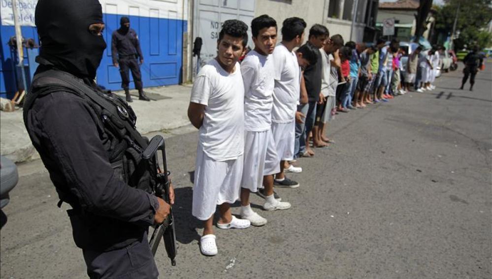 Agentes de la Policía Nacional Civil (PNC) custodian a pandilleros del Barrio 18