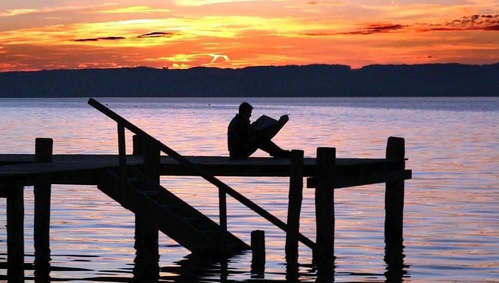 Un hombre lee en un muelle del lago Ammersee en Alemania.