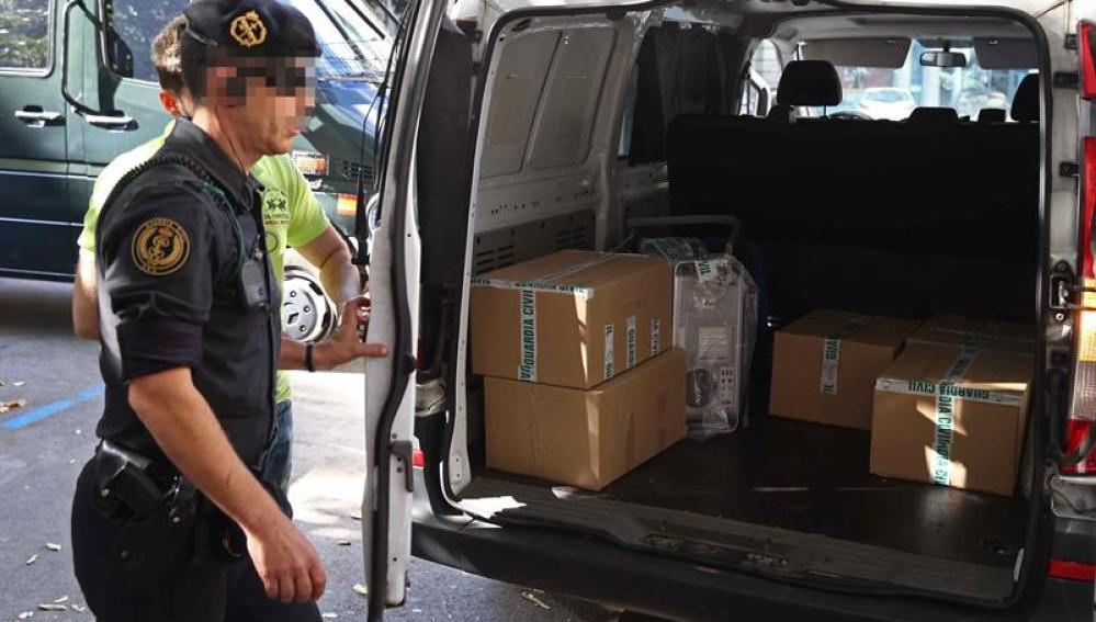 Agentes de la Guardia Civil retiran el material recogido durante el registro efectuado en la sede de la fundación CatDem de CDC.