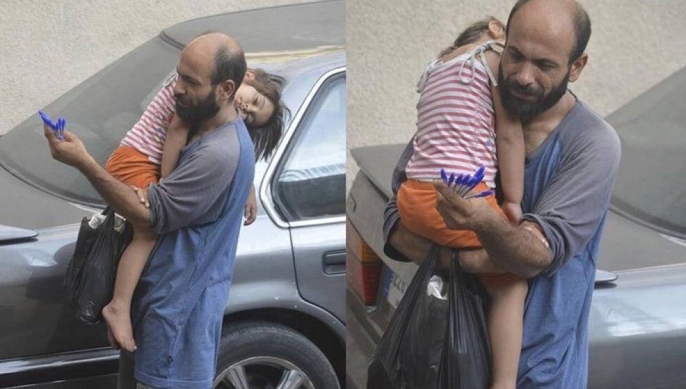 El padre junto a su hija en brazos vendiendo bolígrafos en la calle.