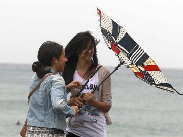 Imagen de archivo de dos jóvenes con el paraguas del revés por el fuerte viento