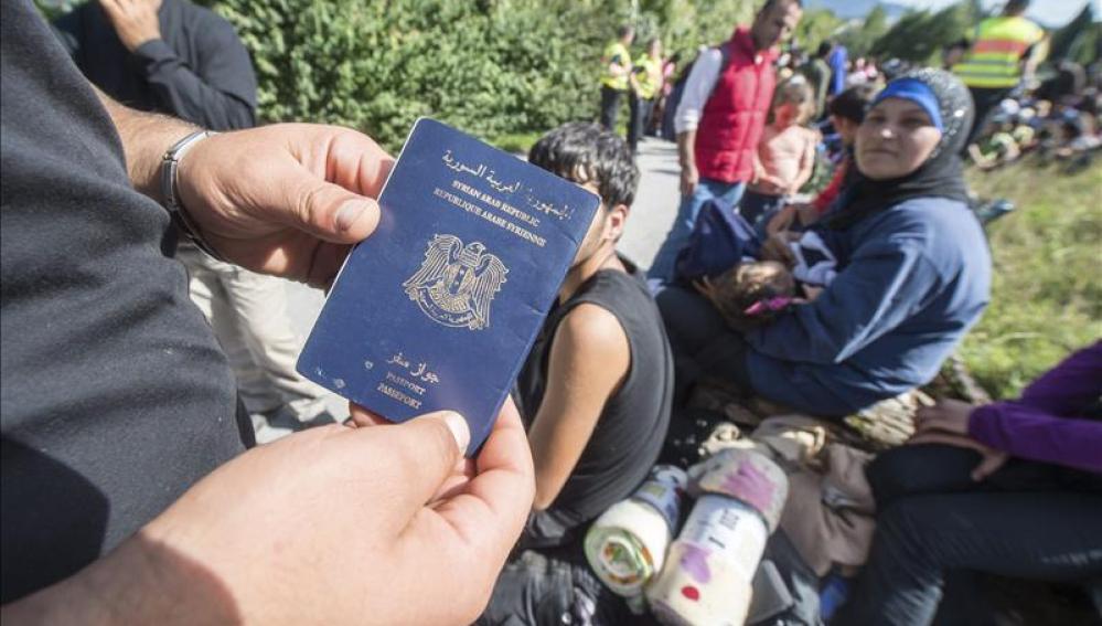Un refugiado enseña su pasaporte sirio mientras espera para cruzar la frontera