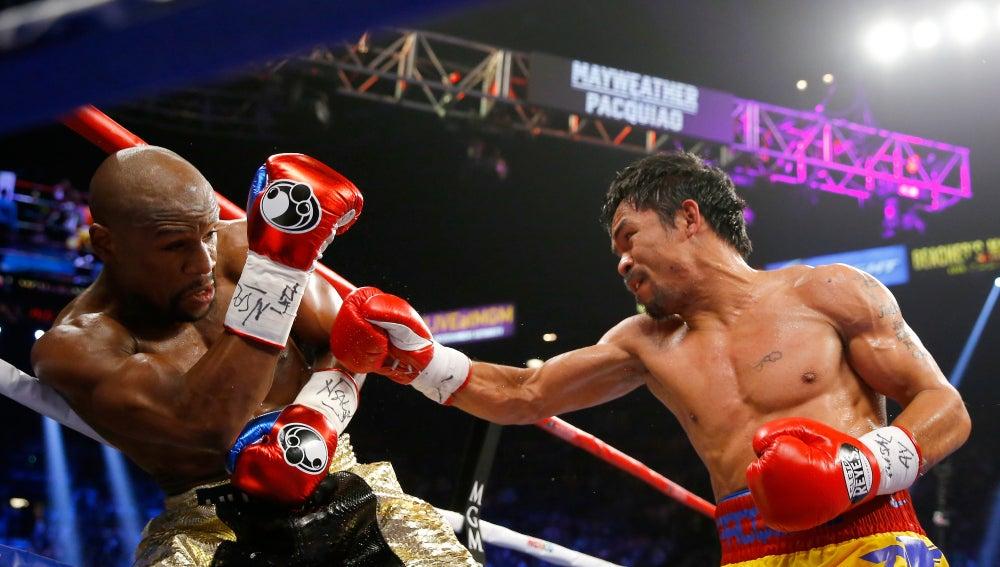Manny Pacquiao (d) lanza un puñetazo a Floyd Mayweather (izq)