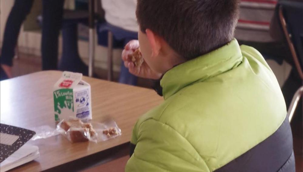 Un niño come solo en el colegio