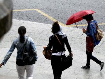 Paseantes tratan de cubrirse de las fuertes lluvias con paraguas