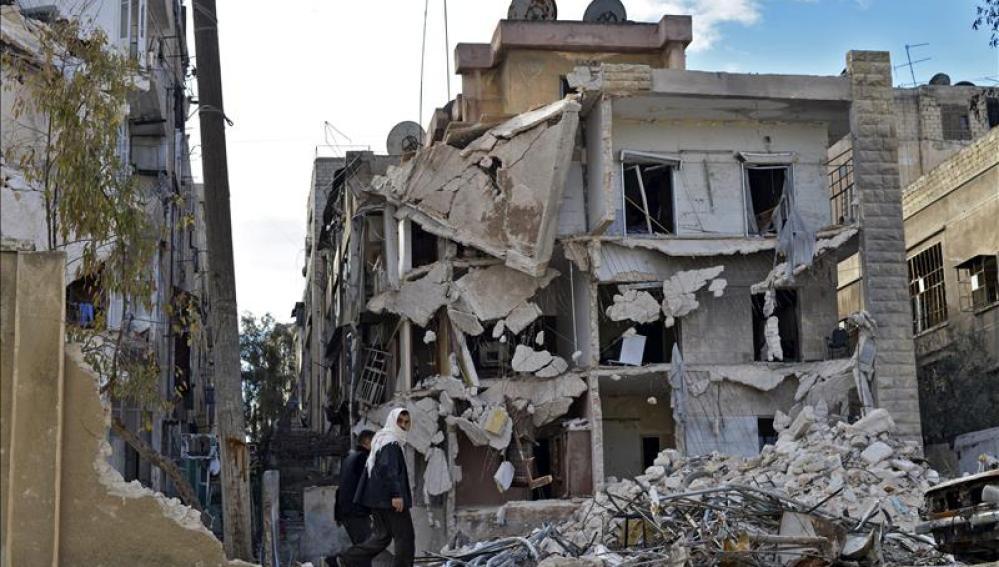 Varios civiles pasando por un edificio destruído por los bombardeos en Alepo, Siria.