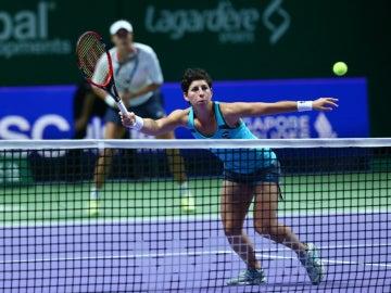 Carla Suárez ataca una bola en la red ante la mirada de Muguruza