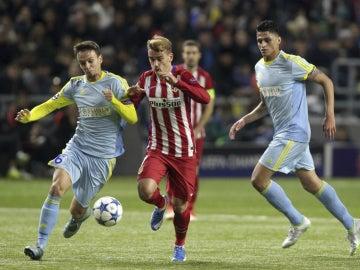 Griezmann conduce el balón ante la oposición del rival