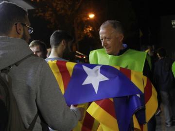 Un voluntario reparte banderas independentistas a la afición en los exteriores del Camp Nou