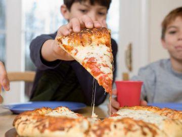 Niños comiendo pizza