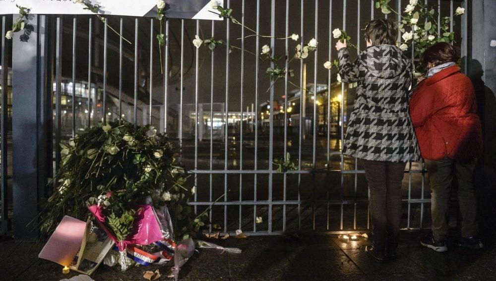 Varias personas depositan flores en homenaje a las víctimas en el Estadio de Francia