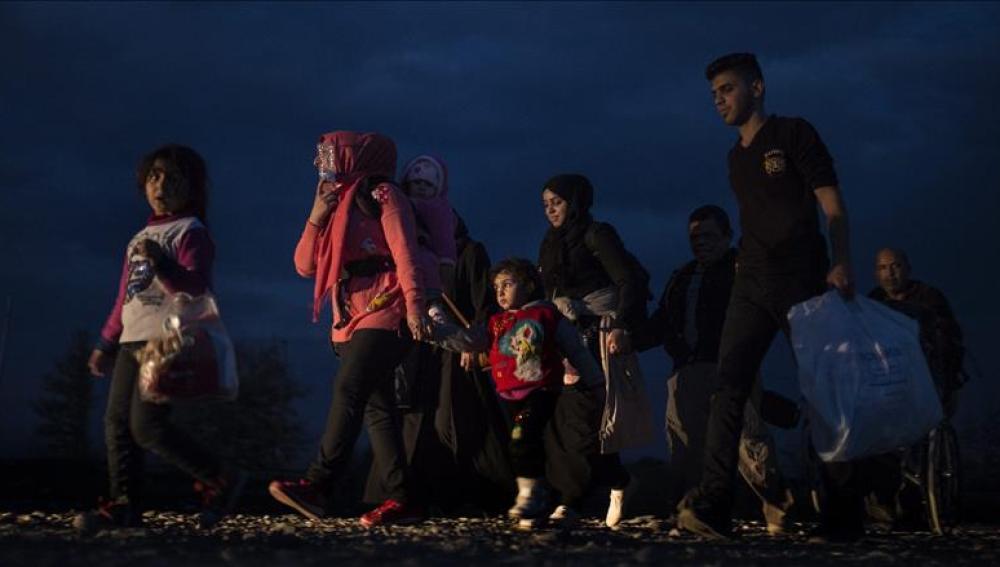 Varios refugiados caminan hacia un campamento de registro y tránsito