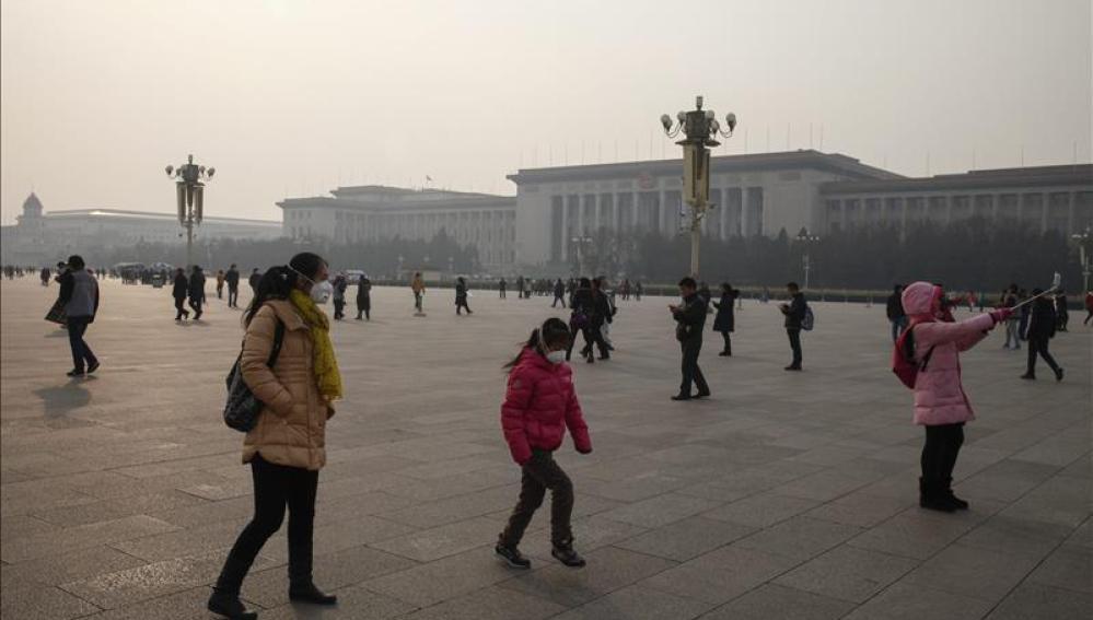 Los viandantes usan máscaras protectoras mientras recorren la plaza de Tiananmen en Beijing, China