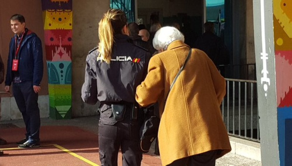 Una anciana acompañada de un agente de policía