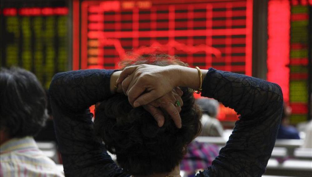 Una mujer comprueba la evolución de la bolsa de Shangái (China)