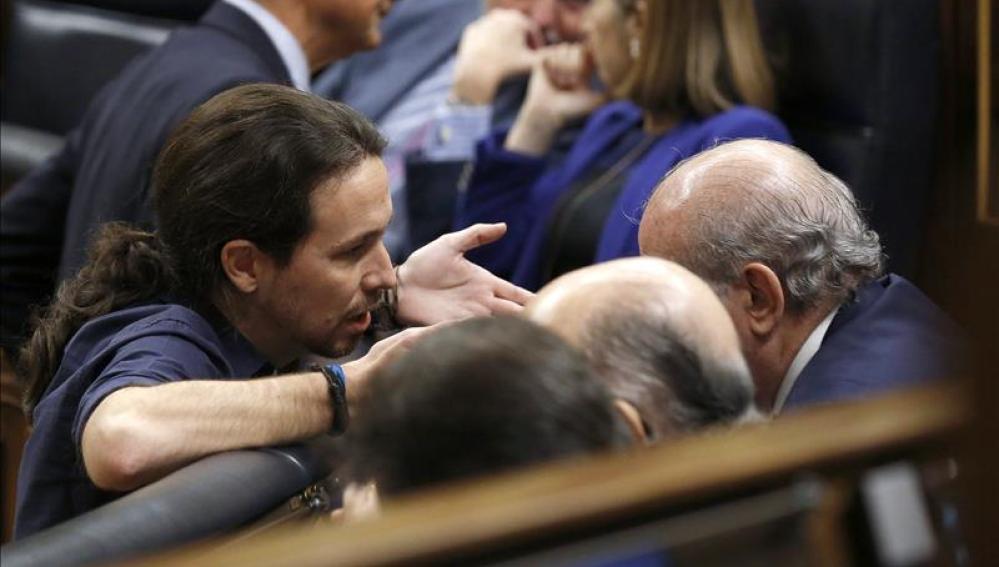Pablo Iglesias conversa con el ministro en funciones del Interior, Jorge Fernández Díaz