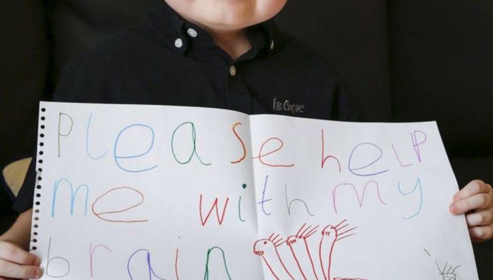 Jamie-lee Dearing con un cartel en el que pide ayuda para tratar su tumor cerebral
