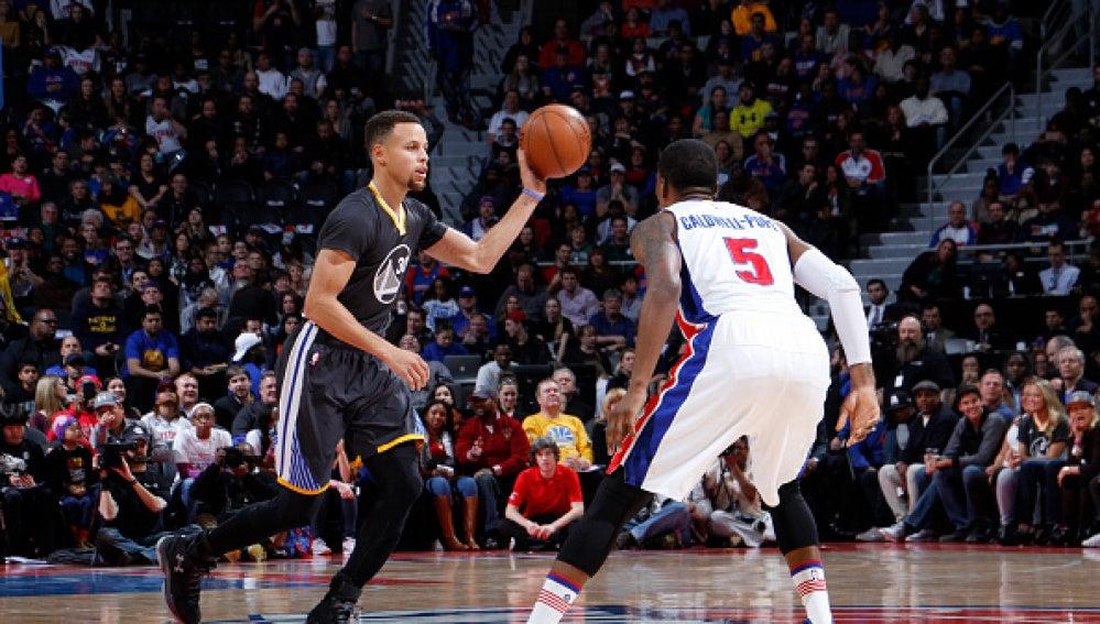 Stephen Curry conduce el balón ante la defensa de Caldwell-Pope