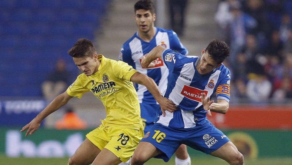 Denis Suárez lucha ante dos jugadores del Espanyol