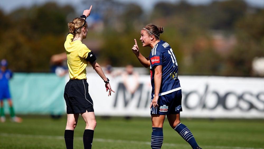 Una árbitro señala una acción durante un partido de fútbol