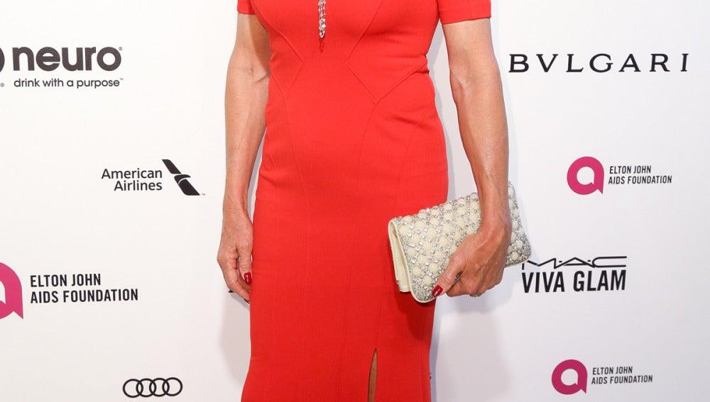 Caitlyn Jenner con vestido rojo y clutch en crema