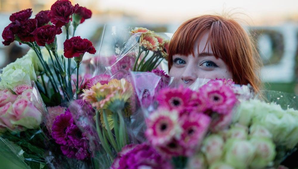 La flores rodean a una joven por primavera