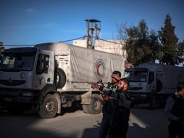 Dos hombres vigilaban los camiones de Naciones Unidas con ayuda humanitaria