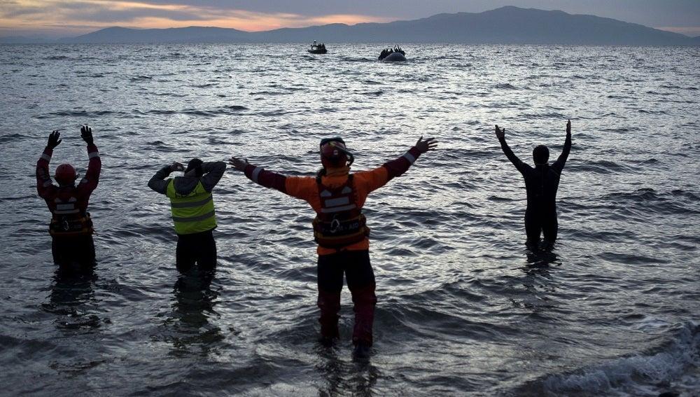 Varios voluntarios aguardan en la costa a la llegada de refugiadosVarios voluntarios aguardan en la costa a la llegada de refugiados